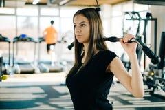 Konditionkvinna i idrottshallen Den unga kvinnan som gör kondition, övar i idrottshallen med latmaskinen Arkivbilder