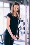 Konditionkvinna i idrottshallen Den unga kvinnan som gör kondition, övar i idrottshallen, med lottmaskinen Royaltyfri Fotografi
