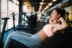 Konditionkvinna i sportkläder med den perfekta sexiga konditionkroppen i idrottshall royaltyfri fotografi
