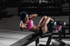 Konditionkvinna i sportkläder med den perfekta sexiga kroppen i idrottshall