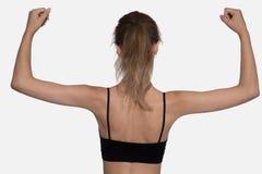 Konditionkvinna i svart tillbaka till kamerahänder upp på vit backgroud Royaltyfri Bild