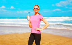 Konditionkvinna med ett plast- flaskvatten på stranden Royaltyfri Fotografi