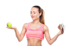 Konditionkvinna med preventivpillerar i en hand och grönt äpple i andra Royaltyfria Bilder