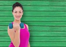 konditionkvinna med vikt med grön wood bakgrund Fotografering för Bildbyråer