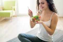 Konditionkvinna som äter sund mat efter genomkörare arkivbild