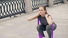 Konditionkvinna som använder sportexpanderen för squatting på utomhus- konditionutbildning stock video