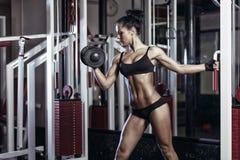 Konditionkvinna som gör övningar med hanteln i idrottshallen royaltyfria bilder