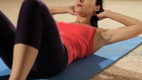 Konditionkvinna som gör buk- knastranden Färdig modell som gör buk- knastranden i en idrottshall stock video