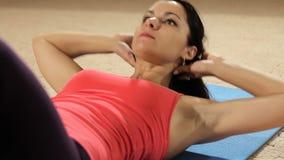 Konditionkvinna som gör buk- knastranden Färdig modell som gör buk- knastranden i en idrottshall Närbild stock video