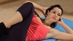 Konditionkvinna som gör buk- knastranden Färdig modell som gör buk- knastranden och sparkar henne ben i en idrottshall Närbild lager videofilmer