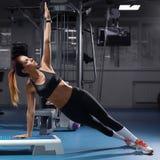 Konditionkvinna som gör plankövningen på idrottshallen, sportig flickagenomkörare royaltyfri fotografi