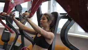 Konditionkvinna som inomhus gör bröstkorgelevatorn på maskinen i idrottshall arkivfilmer