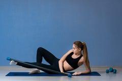 Konditionkvinna som ligger på matta görande övningar för en yoga royaltyfri bild