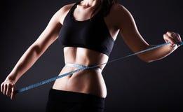 Konditionkvinna som mäter hennes midja, viktförlust Royaltyfri Foto
