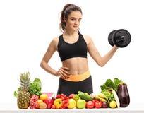 Konditionkvinna som rymmer en hantel bak en tabell med frukt och v Fotografering för Bildbyråer
