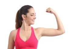 Konditionkvinna som ser hennes bicepsmuskel royaltyfri fotografi