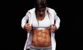 Konditionkvinna som ser hennes muskulösa abs Royaltyfri Foto