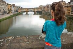 Konditionkvinna som ser på pontevecchio i florence Arkivbild