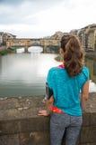 Konditionkvinna som ser på pontevecchio i florence, Italien baksida Arkivfoton