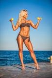 Konditionkvinna som utarbetar på stranden i sommar royaltyfri bild