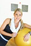 Konditionkvinna som vilar efter övningar i idrottshall Royaltyfri Foto