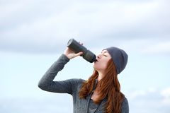 Konditionkvinnadricksvatten från flaskan utomhus Royaltyfria Foton