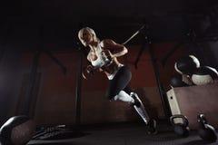 Konditionkvinnagenomkörare på TRXEN i idrottshallen Royaltyfri Fotografi