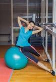 Konditionkvinnan i idrottshall som vilar på pilates, klumpa ihop sig Ung kvinna som gör övning på konditionboll Flicka med kondit Arkivfoto