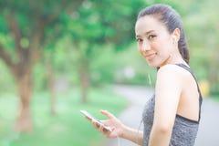 Konditionkvinnan lyssnar till musik från hennes mobiltelefon medan royaltyfri foto