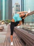 Konditionkvinnan som gör fot, höjde push-UPS på en bänk i staden Sportig flicka som utomhus övar arkivfoton