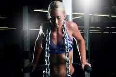 Konditionkvinnan som gör triceps, övar i idrottshallen med en metallkedja Royaltyfri Fotografi