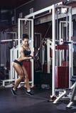 Konditionkvinnan som gör triceps, övar i idrottshallen Royaltyfri Fotografi