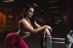 konditionkvinnan står nära den utbildande apparaturen som poserar i idrottshallen royaltyfri bild