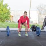 Konditionkvinnan utbildar deadlift på idrottshallen Arkivbild