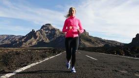 Konditionkvinnaspring - löpare på bergvägen lager videofilmer
