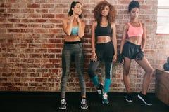 Konditionkvinnor som står i idrottshall Arkivfoton