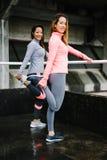 Konditionkvinnor som sträcker ben Arkivfoto