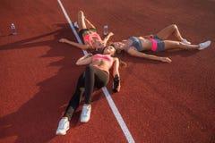 Konditionkvinnor som vilar på golv Trötta idrottsman nen som tillsammans ligger efter en idrottshallgenomkörare i cirkel i stadio Arkivfoto