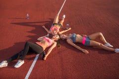 Konditionkvinnor som vilar på golv Trötta idrottsman nen som tillsammans ligger efter en idrottshallgenomkörare i cirkel i stadio Royaltyfri Foto