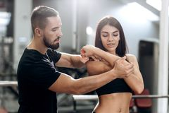 Konditionlagledareexplans till iklädd svart sportkläder för idrotts- flicka hur arbetar muskler av armarna fotografering för bildbyråer