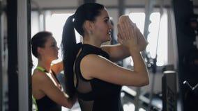 Konditionlagledaren och hennes klient värmer deras armar i idrottshall upp lager videofilmer