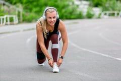 Konditionlivsstil Den unga kvinnan, i hörlurarband, snör åt, innan han joggar r sund livstid f?r begrepp royaltyfri fotografi