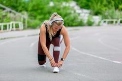 Konditionlivsstil Den unga kvinnan, i h?rlurarband, sn?r ?t, innan han joggar r sund livstid f?r begrepp fotografering för bildbyråer