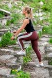 Konditionlivsstil Den unga kvinnan tar upp ett moment r sund livstid f?r begrepp fotografering för bildbyråer