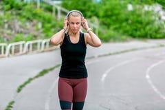 Konditionlivsstil Trettio-år-gamla körningar för ung kvinna i hörlurar r sund livstid f?r begrepp royaltyfri foto