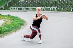 Konditionlivsstil Ung kvinna som gör sidoutfall med en vänd r sund livstid f?r begrepp arkivfoto