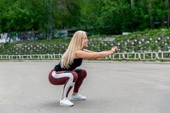 Konditionlivsstil Ung kvinna som g?r squats r sund livstid f?r begrepp f?r bildfoto f?r kustlinje gr?n horisontalf?r sardinia veg arkivbilder