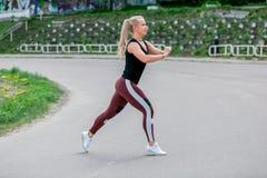 Konditionlivsstil Ung kvinna som g?r utfall i ett hopp r sund livstid f?r begrepp arkivbilder