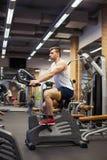 Konditionman på cykeln som gör snurr på idrottshallen Färdig ung man som utarbetar på idrottshallcykeln royaltyfria bilder