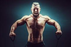 Konditionman som övar med sträckning av musikbandet Muskulös sportman som övar med den elastiska gummibandet Utarbeta för grabb Royaltyfri Fotografi